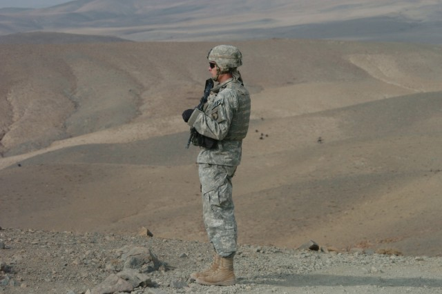 Staff Sgt. Norman Bone, a patrol leader for the 561st Military Police Company, attached to 10th Mountain Division, assesses the area for a security perimeter near Bagram, Afghanistan.