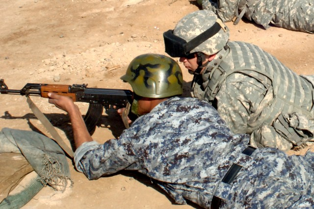 A Soldier from the 2nd Brigade Combat Team, 2nd Infantry Division, attached to the 4th Brigade, 1st National Police Division Transition Team, supervises an Iraqi police officer from the 4th Brigade, 1st National Police Division during training at the marksmanship range at Camp Rustamiyah Dec. 2.