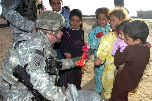 Capt. Jason Arnold, from Military Transition Team 2, hands out toys to children in a small village in Salah Ad Din Province, Iraq.