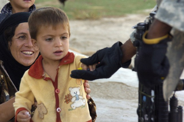 An Iraqi boy takes a piece of candy from a Soldier with Company A, 2nd Battalion, 35th Infantry Regiment, 25th Infantry Division during a dismounted patrol in Tawiliah village near Kirkuk.