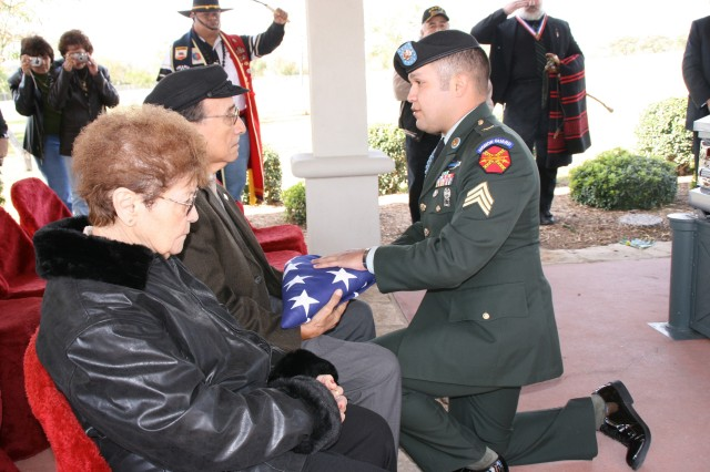 Sgt. Alejandro Deluna from the Honors Platoon, U.S. Army Garrison, presents the U.S. flag to Armando Aguirre, a traditional part of a military funeral.