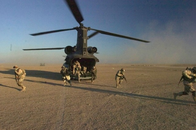 The Iraqi soldiers exit the Chinook and take up positions around the perimeter of their landing zone at the commencement of the operation.