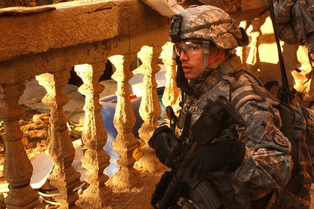 1st Lt. Jeff Harris, a platoon leader from A Troop, 1st Squadron, 40th Cavalry Regiment, takes cover during a cordon and search mission for IED bomb makers in the Hawr Rajab section of Baghdad.