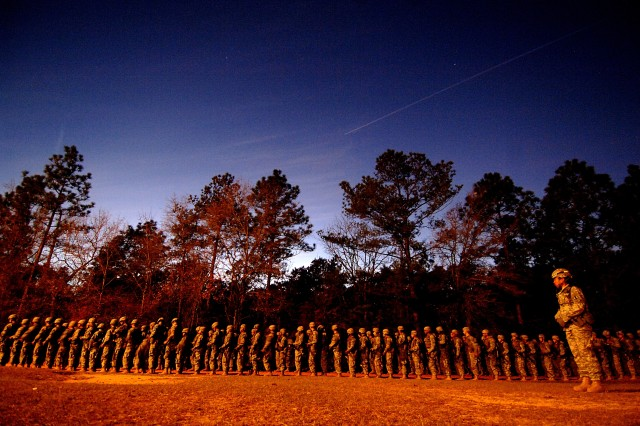 A U.S. Army basic training instructor, right, watches over recruits that are lined up waiting to begin their night infiltration course during U.S. Army basic training at Fort Jackson, S.C., Dec. 5, 2006.