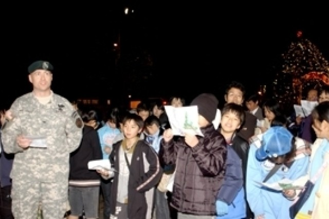Col. Robert M. Waltemeyer, commander of U.S. Army Garrison Japan, sings Christmas carols along with neighborhood locals in front of Kosei Hospital shortly after the tree lighting ceremony Friday at Sagami General Depot.
