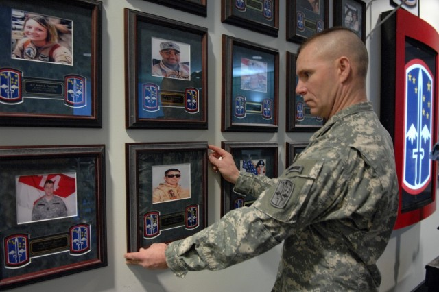 Sgt. 1st Class Cole Shepherd straightens a portrait of one of a fallen soldier prior to a Memorial Wall dedication honoring fallen 172nd Stryker Brigade soldiers at Fort Wainwright, Alaska, Dec. 12, 2006