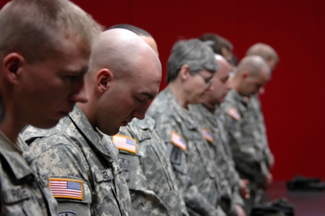 Soldiers bow their heads during the benediction during a Memorial Wall dedication honoring fallen members of the 172nd Stryker Brigade at Fort Wainwright, Alaska, Dec. 12.