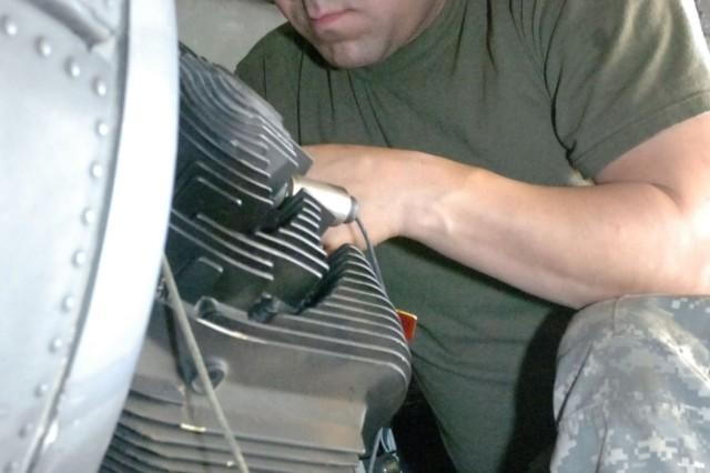 Spc. Daniel Acevedo checks all the wires inside an Apache's nose gearbox.