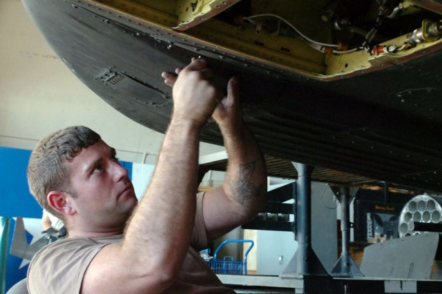 Spc. Brandon Buchanan places a panel back on the Apache. The panel protects the helicopter's communication equipment.