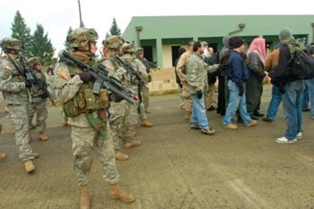 """Soldiers from B Co., 4-9 Inf. move up a street during a raid in Leschi Town. The raid was part of the 4th Bde., 2 Inf. Div. """"Cascadian Commitment"""" exercise."""