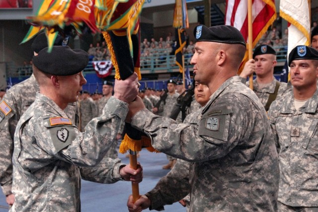Maj. Gen. Charles H. Jacoby Jr., left, receives the brigade colors from outgoing commander Col. Michael H. Shields during the 172nd Stryker Brigade Combat Team and 1st Stryker Brigade Combat Team, 25th Infantry Division's reflagging/change of command ceremony in Fairbanks, Alaska, Dec. 14, 2006. Col. Burdett Thompson is the new commander for the 1st Brigade.
