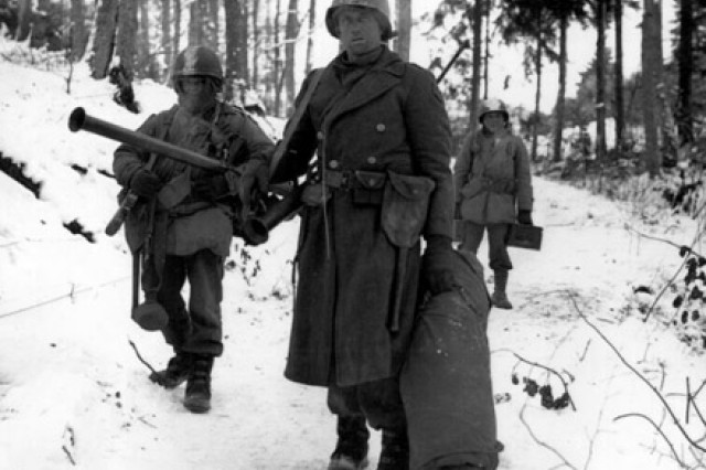 American engineers emerge from the woods and move out of defensive positions after fighting in vicinity of Bastogne, Belgium.