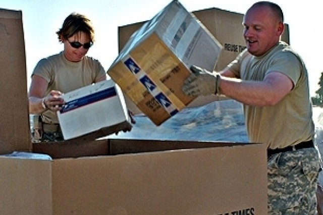 Spc. Tammy Wasinger and Staff Sgt. Nathan Brasel of the 747th Adjutant General Company Postal, a Reserve unit from Helena, Mont., sort mail at the Forward Operating Base Warrior post office. The post office is expected to handle 50 percent more mail over the holiday season.