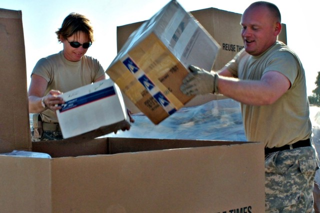 Spc. Tammy Wasinger and Staff Sgt. Nathan Brasel of the 747th Adjutant General Company, a reserve unit from Helena, Mont., sort mail at the Forward Operating Base Warrior post office. The post office expects a 50 percent increase in mail during the holiday season.