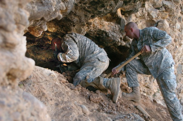 Command Sgt. Maj. Eugene Spencer (left), uses a pick to dig inside a cave suspected of containing a cache, as Sgt. Michael Schobey shovels away the loose dirt.
