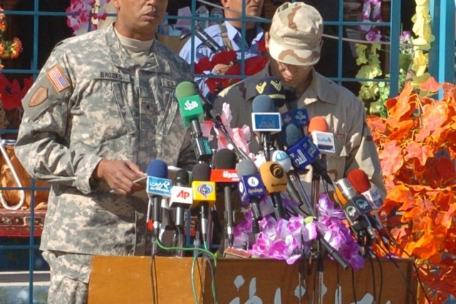 Brig. Gen. Vincent Brooks, deputy commanding general - support for Multinational Division - Baghdad, with his interpreter, addresses an audience of several hundred Iraqis at a transfer to Provincial Iraqi Control ceremony in Najaf, Iraq Dec. 20.