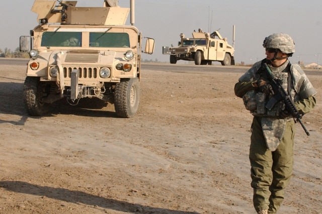 Soldiers from Troop D, 1st Battalion, 82nd Field Artillery Regiment patrol Taji, Iraq, on foot and in Humvees, Nov. 30, 2006.