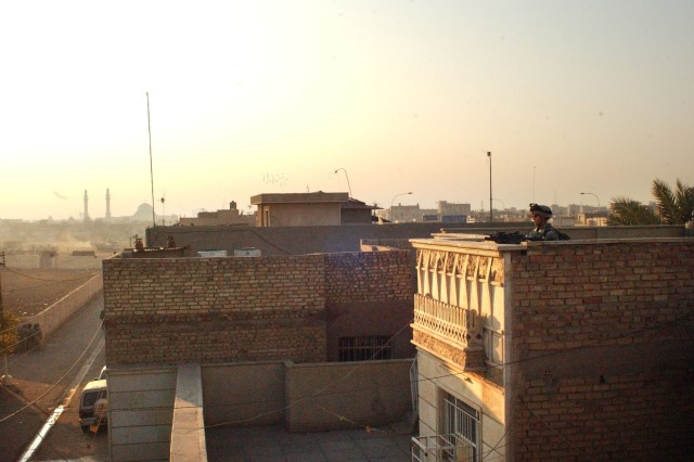 A Soldier finds a good rooftop vantage, where he can readily scout the area for snipers.