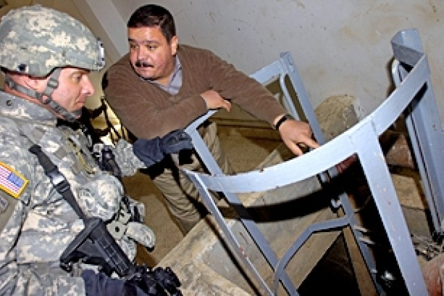 Moshtak Talib Abid, an engineer who maintains the Al Bakr Water Treatment Plant, shows Col. Bryan Owens, commander, 3rd Brigade Combat Team, 82nd Airborne Division, around the plant Nov. 28, 2006, in Al Bakr, Iraq.
