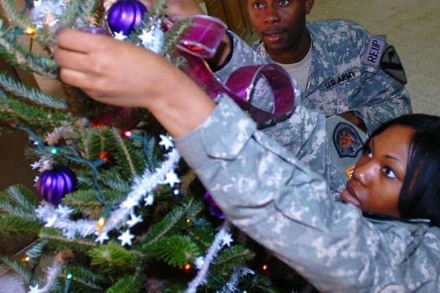 Sgt. Rosie Threatt hangs a decoration on the tree as Staff Sgt. Jamile Dingle looks on. Both are from the 1st Air Cavalry Brigade, 1st Cavalry Division, now in Taji, Iraq.
