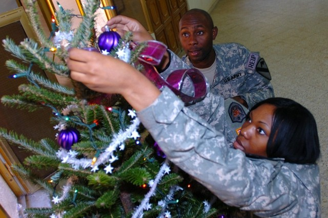 Sgt. Rosie Threatt and Staff Sgt. Jamile Dingle decorate one of the two Fraser firs donated by Jim and Beth Nickelson of Ludington, Mich.