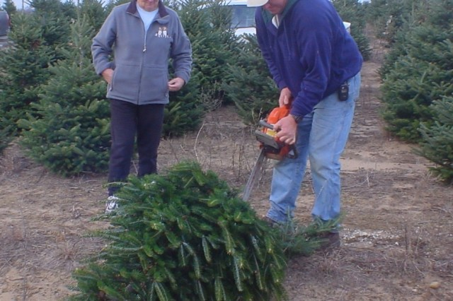 Jim Nickelson, and wife Beth, cut a Fraser fir for Soldiers from 1st Air Cavalry Brigade, deployed to Taji, Iraq.