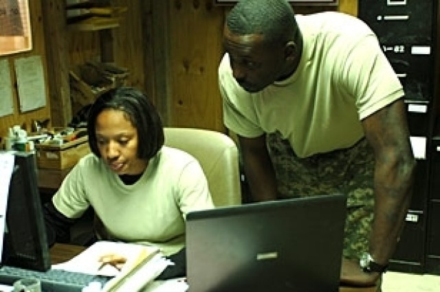Spc. Lakisha Long, a stock control clerk, and Sgt. Lazarus Cromartie, the warehouse assistant noncommissioned officer in charge, both with Company A, 209th Aviation Support Battalion, review the supply control system at the Supply Support Activity on Contingency Operating Base Speicher, Iraq. Their warehouse stocks many classes of supplies from food items to complete aircraft engines.