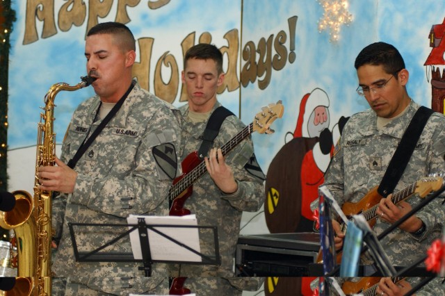 """Staff Sgt. Russell Rennier, Spc. Mitchell Vandenburg and Sgt. Juan Rosaly perform a Christmas melody for Soldiers at Camp Liberty, Iraq, Dec. 23. The Soldiers are members of the group """"Zero Defect,"""" part of the 1st Cavalry Division Band."""