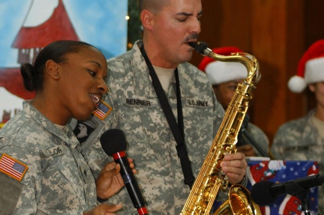 """Spc. Kimberly Taylor and Staff Sgt. Russell Rennier, both members of the group """"Zero Defect,"""" perform Christmas music for troops at Camp Liberty, Iraq, Dec. 23. The group is part of the 1st Cavalry Division Band."""