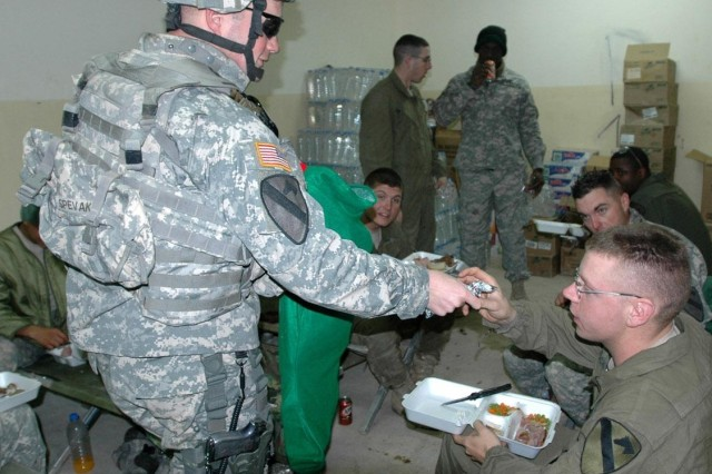 Capt. Adrian Spevak (left), commander, Company B, 2nd Battalion, 8th Cavalry Regiment, hands Pfc. Justin Rockwell a holiday gift from a stocking received from their family readiness group. Spevak, 1st Sgt. Damon Perez and several other Soldiers brought presents to Soldiers at their patrol base in Mushahidah, Iraq.