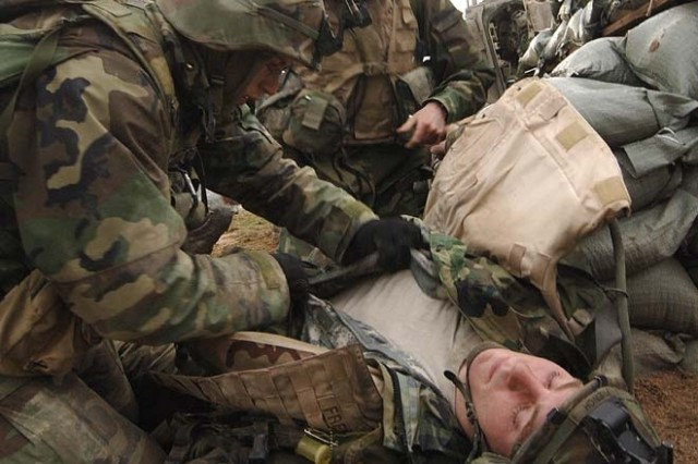 """Soldiers from 3rd Squadron, 2nd Stryker Cavalry Brigade treat an """"injured"""" machine gunner during a defensive exercise at the Grafenwoehr Training Area. The squadron was training in platoon-level engagements, and had to request evacuation of their team member following a hit on his position."""