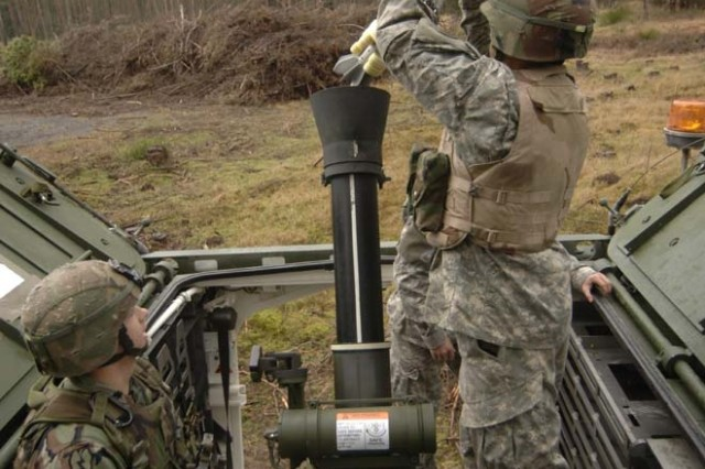 Mortar platoon Soldiers load a 120mm round for supporting fire of 3rd Squadron's defensive engagement in Grafenwoehr Training Area.