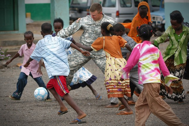 Staff Sgt. Justin Lockhart participates in a game of soccer with students from a Djibouti public school, after handing out school supplies.