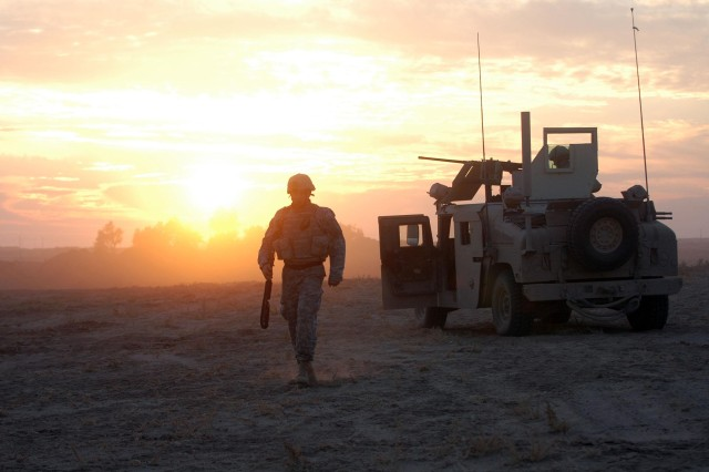 A Paratrooper from the 618th Engineer Support Company (Airborne) walks across the dusty, desert terrain Dec. 9, pulling security on the outskirts of Siniyah, Iraq. The Paratroopers used bulldozers to construct a berm almost around the entire city to isolate terrorists who operate out of it.
