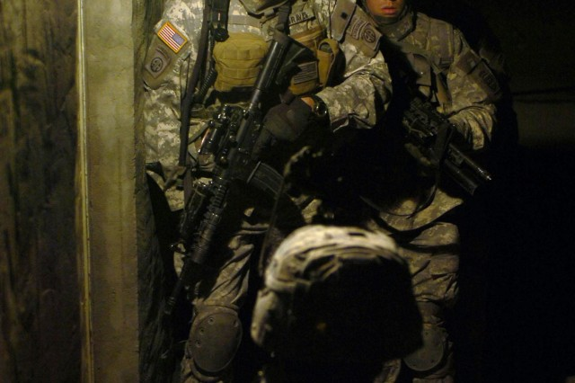Soldiers from Company C, 1st Battalion, 505th Parachute Infantry Regiment, 82nd Airborne Division prepare to breach the entrance of a home during an early-morning raid Dec. 15, in Siniyah, Iraq.