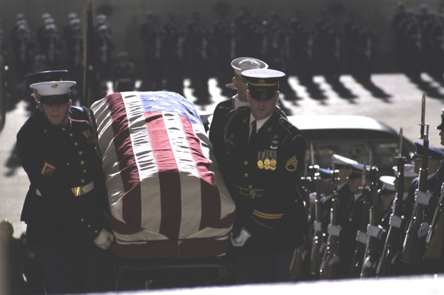 A U.S. military honor guard carries the casket containing the remains of former President Gerald R. Ford up the East Steps of the House of Representatives at the U.S. Capitol building in Washington, D.C., Dec. 30.