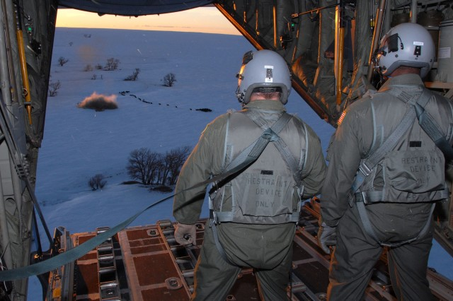 National Guard loadmasters aboard a C-130 Hercules aircraft watch as a 1-ton hay bale lands near a herd of cows during an emergency feeding mission in southeast Colorado Jan. 3. The hay was dropped near La Junta, Colo., to help feed livestock that have been stranded from a snowstorm that has impacted the area.