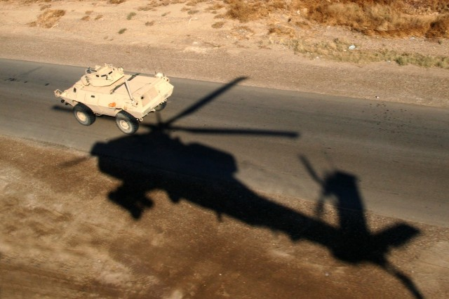 The shadow of an AH-64 Apache helicopter is a reminder that this convoy in Iraq is well protected.