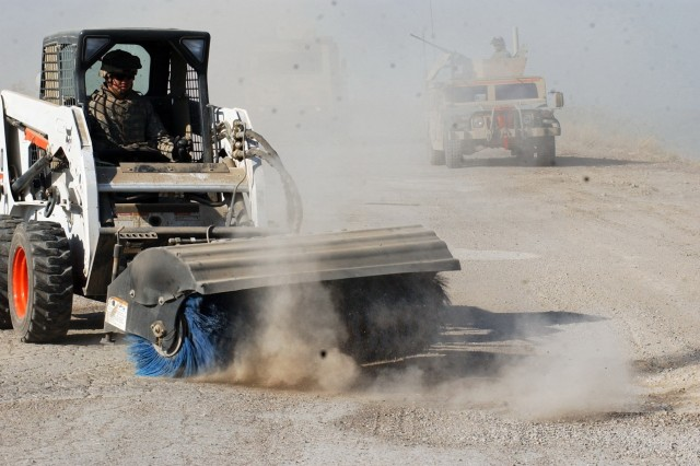 Staff Sgt. William Parker, from the 19th Engineer Battalion, brushes up the streets of Muqdadiyah, Iraq, Dec. 22. His S150 Bobcat loader removes dirt covering previous mine holes, which will be filled with cement to make the route passable.