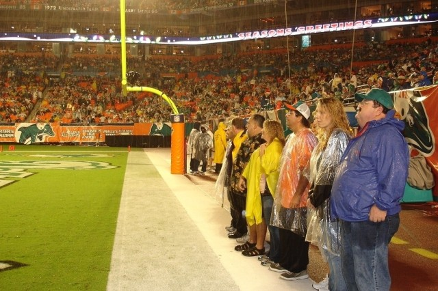 The Ognibene, Baker and Vargas families gather in the Dolphins' end zone during the Army Freedom Team Salute Christmas night in Miami.