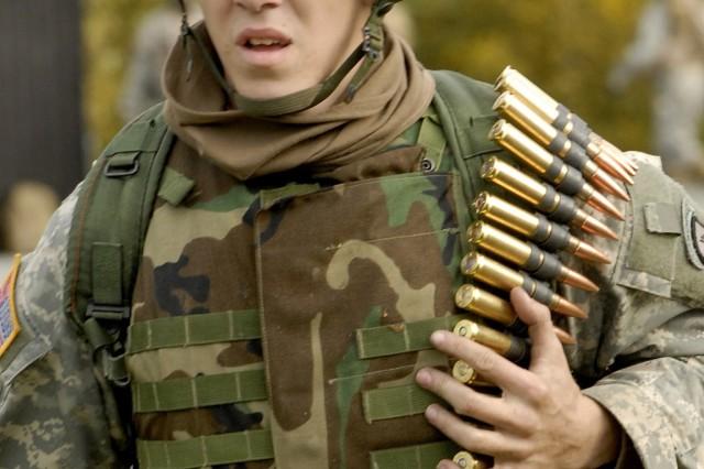 A Soldier carries his .50-caliber ammunition to an M-2 machine gun.