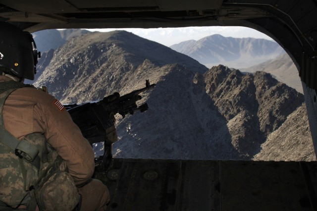 Spc. Tim Parson, from the 158th Aviation Regiment, keeps a lookout aboard a CH-47 Chinook helicopter on the way to conduct a resupply mission for forward operating bases near the village of Naray, Afghanistan, Jan. 5.