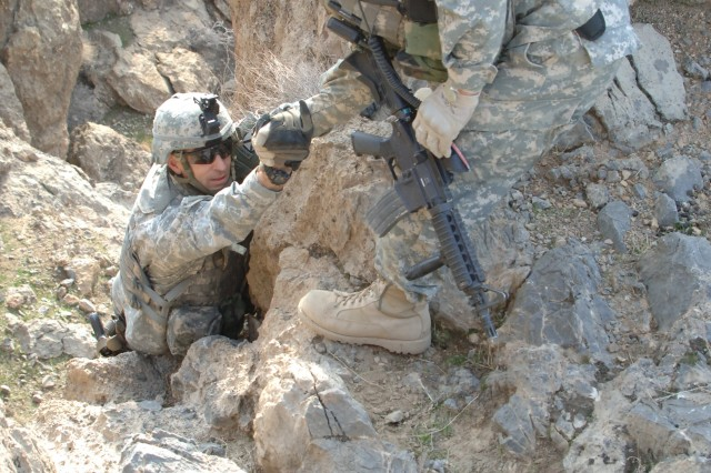 Sgt. Angel Maldonado assists Lt. Col. Michael Price in climbing a cliff to the weapons cache.