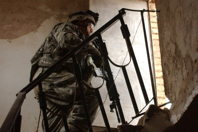 Pfc. Anthony Pardella, from the 501st Parachute Infantry Regiment, searches a house for weapons in Mussayyib, Iraq.