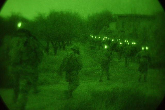 The Soldiers march down a dirt road toward their objectives. The glow sticks on the backs of their helmets enables Soldiers to locate each other using their night vision goggles, which pick up the infrared signature.