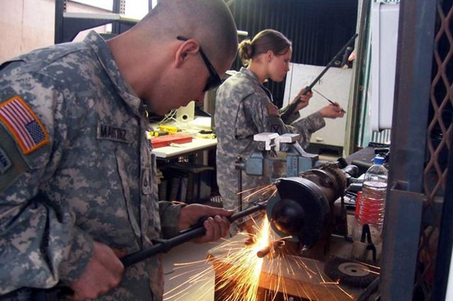 Pfc. Elias Martinez (left) and Pfc. Katrina Nosbich-Stamp, both small arms and artillery repairmen serving with the 210th Brigade Support Battalion, 2nd Brigade Combat Team, 10th Mountain Division, fix weapons at Camp Striker, Iraq.