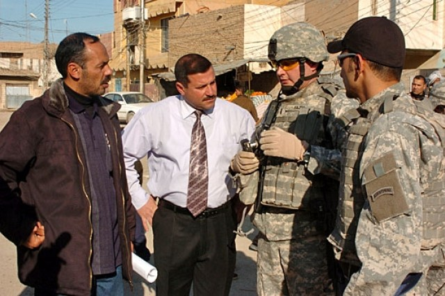 1st Lt. Anthony Fazio (third from left), speaks with city leaders while on a patrol through the Al Zahrah neighborhood on January 4, 2007. Fazio was assessing the area for a proposed $4 million renovation project that would include a new sewage system, drain culverts, sidewalks and paved roads.