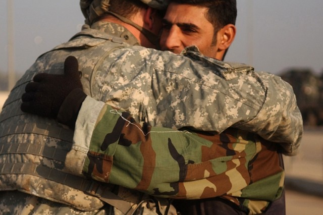 Spc. William Nossaman and an Iraqi policeman wish each other well as the troops begin the operation.
