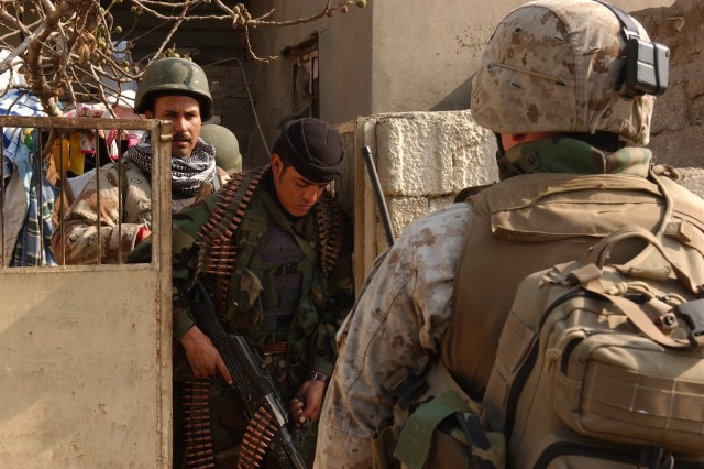 Iraqi police and a Marine clear a house, looking for weapons and insurgents.