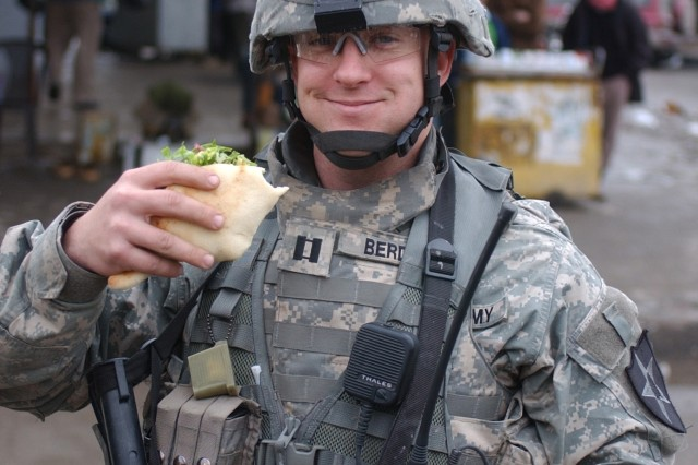 Capt. Jason Berdou, Military Transition Team, enjoys some Iraqi home cooking during a patrol with Iraqi soldiers in the Al Fodle area of east Baghdad.